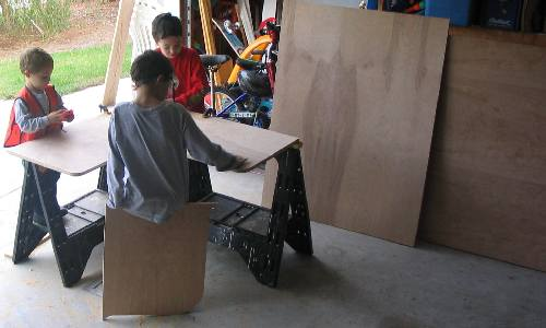 Sons helping with cutting the plywood.