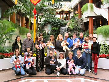9 families in front of an indoor waterfall at the White Swan Hotel