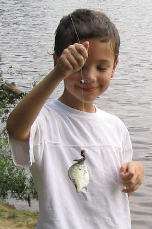 Austin with a small sunfish at the end of the line.